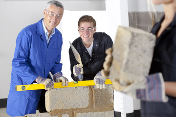 Teacher talking to student using level in bricklaying vocational school