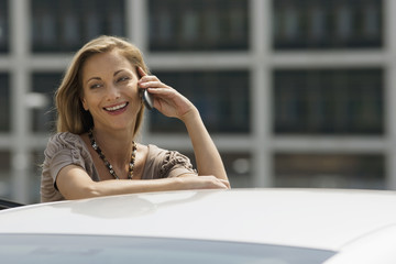 Businesswoman standing beside car, using mobile phone, smiling
