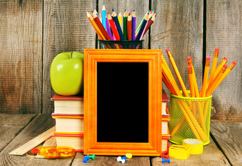 Back to school. Books and school tools on wooden background.