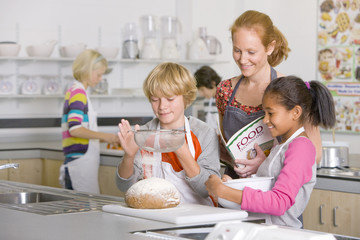 Smiling teacher watching students flouring bread in home economics class