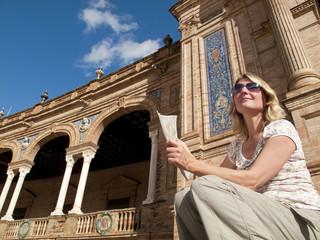 Tourist viewing ornate building in Plaza de Espana, Seville, Spain