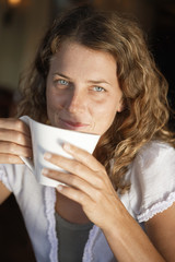 Young woman sipping cup of coffee in cafe, smiling, close-up, portrait