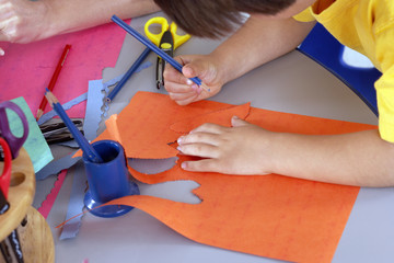 Boy (4-6) cutting shapes out of orange card at desk in classroom, side view, close-up