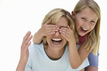 Girl (9-11) covering mother's eyes with hands, laughing, front view, portrait