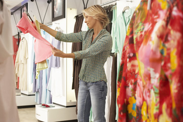 Mature blonde woman shopping in clothes shop, choosing between two different coloured tops, side view