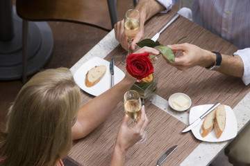 Couple dining in restaurant, man giving woman red rose, elevated view
