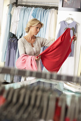 Mature woman shopping in clothes shop, holding red vest top, thinking, focus on background (tilt)