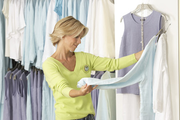 Mature woman shopping in clothes shop, comparing two tops on coathangers, side view