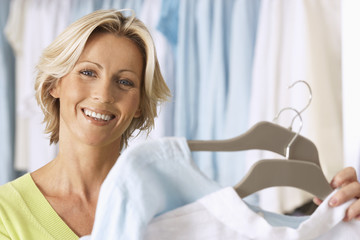 Mature woman shopping in clothes shop, holding two tops on coathangers, smiling, close-up, portrait