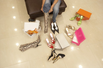 Woman trying on different pairs of high heels and boots in shoe shop, low section, elevated view