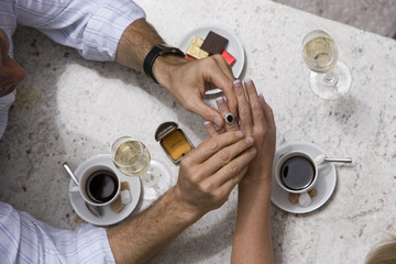 Couple dining in restaurant, man placing engagement ring on woman's finger, overhead view