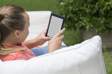 Girl using digital tablet on outdoor sofa