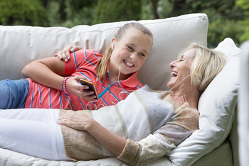 Smiling grandmother and granddaughter laying on outdoor sofa with mp3 player