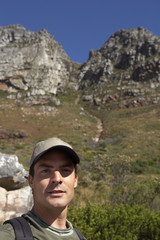 Man standing in valley, rocks in background, portrait