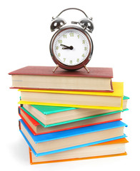 Alarm clock and multi-coloured books.