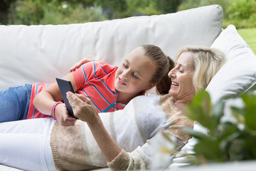 Smiling grandmother and granddaughter laying on outdoor sofa with digital tablet
