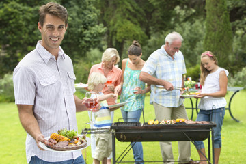 Portrait of smiling man with plate of barbecue and wine glass with family in background