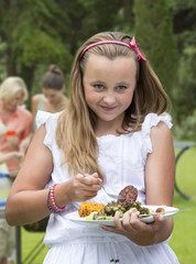 Portrait of smiling girl holding plate of barbecue