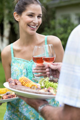 Smiling father and daughter holding plates of barbecue and toasting wine glasses
