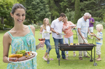 Portrait of smiling woman holding plate of barbecue and glass of wine with family in background