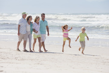 Multi-generation family walking on sunny beach