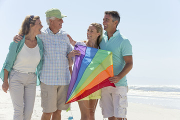 Happy couples with kite on sunny beach