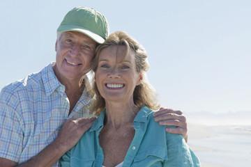 Close up portrait of smiling senior couple on sunny beach