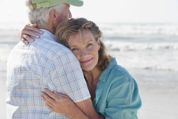 Happy senior couple hugging on sunny beach