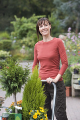 Woman shopping in garden centre, pushing trolley full with pot plants, smiling, portrait