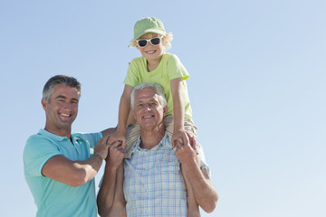 Portrait of smiling multi-generation men against blue sky