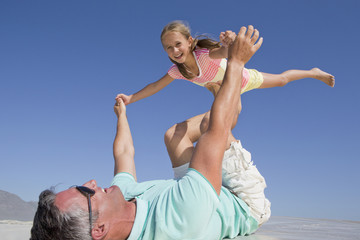 Father lifting daughter on sunny beach