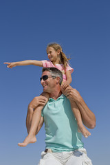 Father carrying daughter on shoulders against blue sky