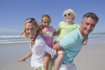 Portrait of smiling parents piggybacking children on sunny beach