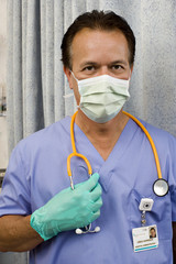 Doctor wearing surgical scrubs, gloves and mask, holding stethoscope, front view, close-up, portrait