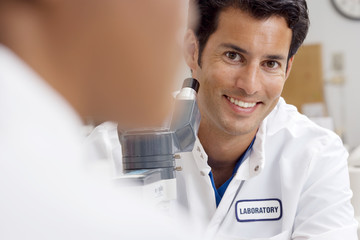 Technicians sitting beside microscope in hospital lab, smiling, portrait, focus on man in background