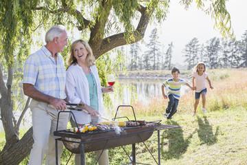 Grandparents Serving Grandchildren At Family Barbeque