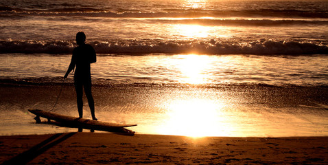 Ocean sunset on the Beach with a silhouette surfer