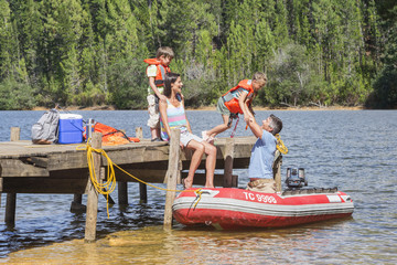 Family Getting Into Inflatable Boat For Fishing Trip
