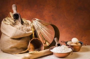 still life con cereali,farina,spighe e utensili da cucina