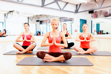group of smiling feamle meditating in the gym