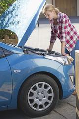 Woman With Broken Down Car Looking Under Bonnet