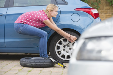 Woman Changing Flat Tyre On Car