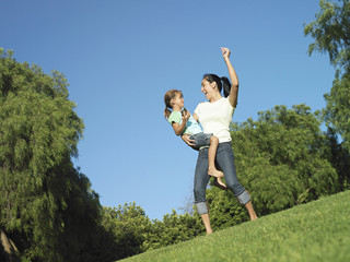 Mother and daughter (6-8) dancing on grass in park, girl holding MP3 player, surface level (tilt)