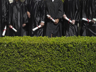 Row of university students in graduation gowns holding diplomas, mid-section, hedge in foreground