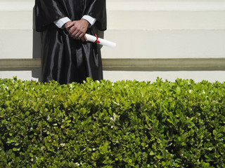 University student in graduation gown holding diploma, mid-section, hedge in foreground