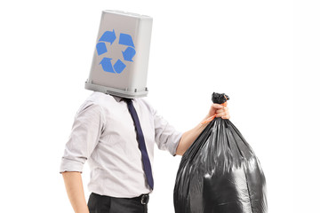 Man with a recycle bin over his head carrying a garbage bag