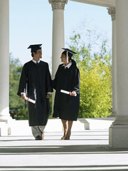 University students in graduation gowns and mortar boards walking in colonnade, holding diplomas
