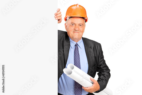 Mature construction worker standing behind panel