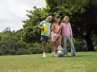 Three girls (7-9) standing on grass in park with frisbee, soccer ball and skipping rope, portrait