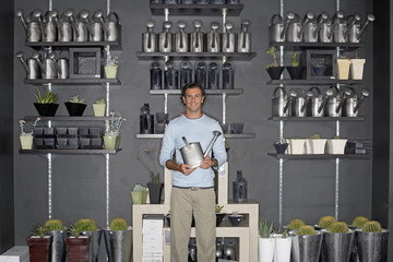 Man standing beside cacti display in shop, holding watering can, smiling, front view, portrait